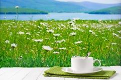 Kaffeetasse gegen blühende Wiese Lizenzfreies Stockfoto