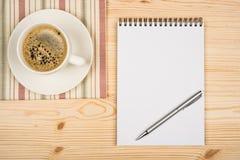 Kaffeetasse, gewundenes Notizbuch und Feder Lizenzfreie Stockfotos