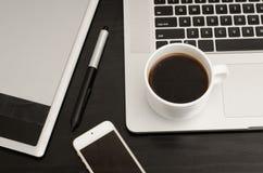 Kaffeetasse, Grafiktablette mit einem Griffel, Teil des Laptops und Telefon auf schwarzem Holztisch, Nahaufnahme Lizenzfreie Stockfotografie