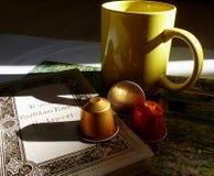 Kaffeetasse, Kaffee kapselt ein Buch und Schatten ein stockfotografie