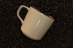 Kaffeetasse, Kaffeebohnen und hölzerne Tischplatteansicht stockfotos