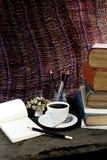 Kaffeetasse, Kompass und Bleistift der alten Bücher auf einem hölzernen Stockfotos