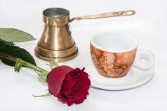 Kaffeetasse, kupferner Topf und Rotrose Stockbild