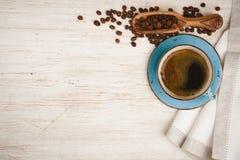 Kaffeetasse, Löffel mit Bohnen und Tischdecke auf Holztisch stockfotos