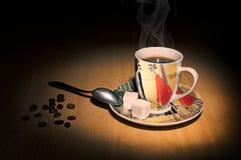 Kaffeetasse, Löffel und Kaffeebohnen auf einem Holztisch lizenzfreie stockbilder