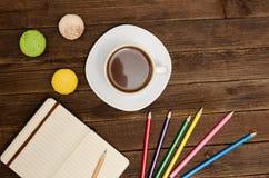 Kaffeetasse, macarons, färbte Bleistifte und einen Notizblock auf einem hölzernen Hintergrund Lizenzfreies Stockbild