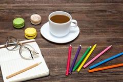 Kaffeetasse, Makronen, färbte Bleistifte und ein Notizbuch Lizenzfreies Stockfoto