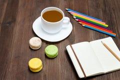 Kaffeetasse, Makronen, färbte Bleistifte und ein Notizbuch auf einem woode Lizenzfreies Stockfoto