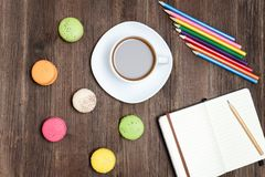 Kaffeetasse, Makronen, färbte Bleistifte und ein Notizbuch auf einem woode Stockfoto