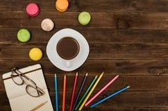 Kaffeetasse, Makronen, färbte Bleistifte und einen Notizblock mit Gläsern auf einem hölzernen Hintergrund Lizenzfreies Stockfoto