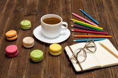 Kaffeetasse, Makronen, färbte Bleistifte und einen Notizblock mit Gläsern auf einem hölzernen Hintergrund Stockbild