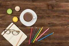 Kaffeetasse, Makronen, färbte Bleistifte und einen Notizblock mit Gläsern auf einem hölzernen Hintergrund Beschneidungspfad einge Lizenzfreies Stockbild