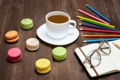 Kaffeetasse, Makronen, färbte Bleistifte und einen Notizblock mit glasse Stockbilder