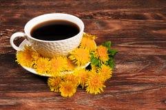 Kaffeetasse mit Blumen auf hölzernem Hintergrund Lizenzfreie Stockbilder