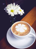 Kaffeetasse mit Blumendekoration des weißen Gänseblümchens auf Holztisch Stockbild
