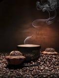 Kaffeetasse mit Bohnen und Muffins lizenzfreie stockfotografie