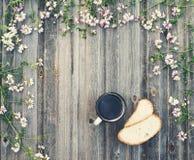 Kaffeetasse mit Brot auf verwittertem hölzernem Hintergrund mit Feld Lizenzfreies Stockbild
