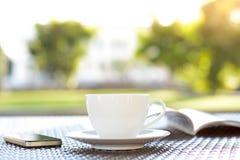 Kaffeetasse mit Buch auf unscharfem grünem Naturhintergrund Stockbild