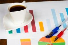 Kaffeetasse mit bunter Bar und Kreisdiagramme und Stifte Lizenzfreies Stockbild