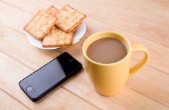 Kaffeetasse mit dem Brot und auf dem Tisch gesetzt. Stockbild