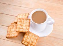 Kaffeetasse mit dem Brot und auf dem Tisch gesetzt. Lizenzfreie Stockfotos