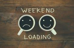 Kaffeetasse mit den traurigen und glücklichen Gesichtern nahe bei Wochenendenladen-Phrasenhintergrund Weinlese gefiltert Glücklic Lizenzfreies Stockfoto