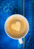 Kaffeetasse mit der Herzform gemacht vom Schaum auf blauem Geschirrtuch stockfotografie