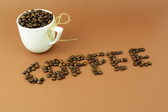 Kaffeetasse mit einem Bogen und einem Kaffeebohnewort Stockfoto