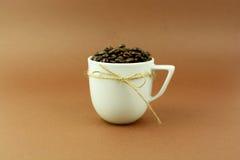 Kaffeetasse mit einem Bogen und Kaffeebohnen brünieren Hintergrund Lizenzfreies Stockbild