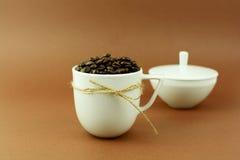 Kaffeetasse mit einem Bogen und Kaffeebohnen mit Zuckerschüssel Lizenzfreies Stockfoto