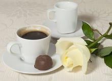 Kaffeetasse mit einer Schokolade und einer weißen Rose Lizenzfreie Stockfotografie