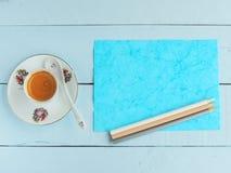 Kaffeetasse mit farbigem Papier und Bleistiften Stockfotografie