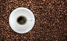Kaffeetasse mit gebratenem Bohnenhintergrund Lizenzfreie Stockfotos