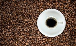 Kaffeetasse mit gebratenem Bohnenhintergrund Stockfotografie