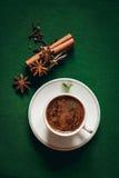Kaffeetasse mit Gewürzen auf grünem Hintergrund Stockbilder