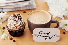 Kaffeetasse mit gutem Morgen des kleinen Kuchens, der Blumen, der Zeitung und der Anmerkungen auf rustikaler Tabelle, Süßspeise z Stockfotografie