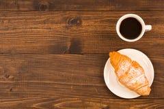 Kaffeetasse mit Hörnchen zum Frühstück auf einem dunklen Holztisch, Draufsicht Stockfotografie