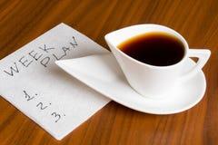 Kaffeetasse mit Handschriftswochenplan auf Serviette Stockbilder
