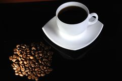 Kaffeetasse mit highlited Kaffeebohnen lizenzfreies stockbild