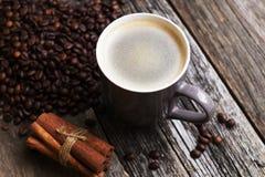Kaffeetasse mit Kaffeebohnen auf hölzernem Hintergrund Stockfotografie