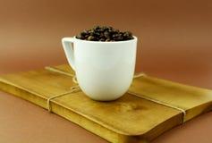 Kaffeetasse mit Kaffeebohnen auf hölzernem Schneidebrett Stockbild