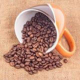 Kaffeetasse mit Kaffeebohnen auf Segeltuch Lizenzfreie Stockfotos
