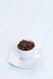 Kaffeetasse mit Kaffeebohnen auf Tabelle Lizenzfreies Stockbild