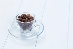 Kaffeetasse mit Kaffeebohnen auf Tabelle Lizenzfreie Stockfotos