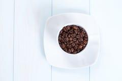 Kaffeetasse mit Kaffeebohnen auf Tabelle Stockbild