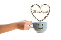 Kaffeetasse mit Kaffeebohnen formte Herz mit Zeichen des guten Morgens Stockfoto