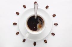 Kaffeetasse mit Löffel auf Untertasse und Kaffeebohnen gegen den weißen Hintergrund, der die Uhrskala angesehen von der Spitze bi Stockfoto
