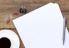 Kaffeetasse mit leerem Blatt Papier auf Schreibtisch Lizenzfreies Stockbild