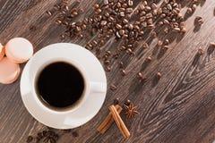 Kaffeetasse mit macarons und Kaffeebohnen Stockfotos