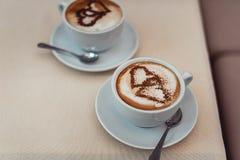 Kaffeetasse mit Milch und Herz formen auf eine Tabelle Stockfotos